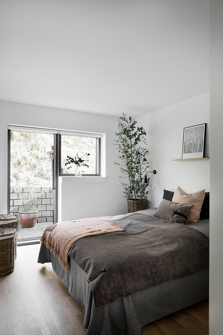 View into simple bedroom with access to garden