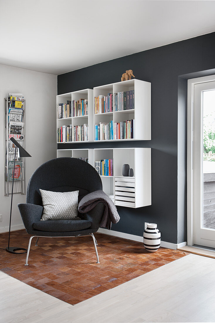 Armchair, magazine rack and wall-mounted shelves in reading area
