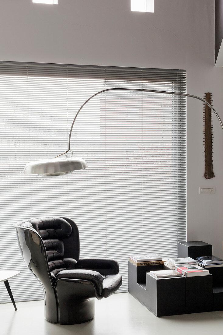 Arc lamp above black designer armchair next to window