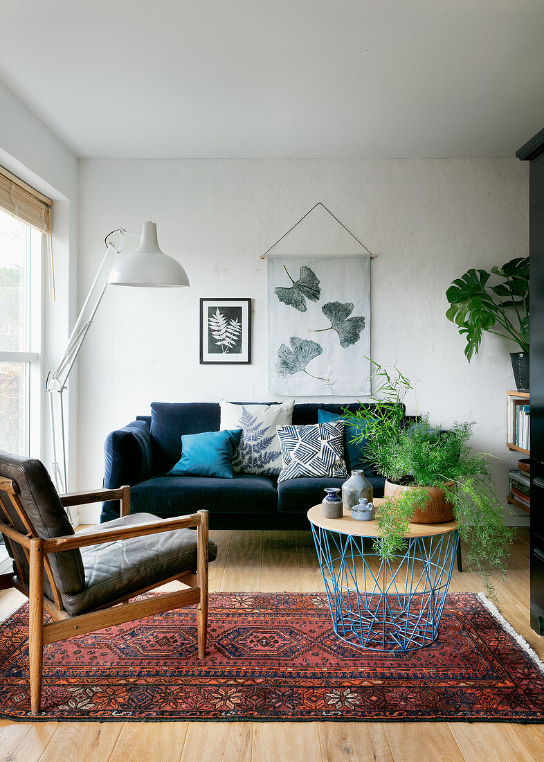 Coffee table with wire basket base in front of blue velvet sofa in living room