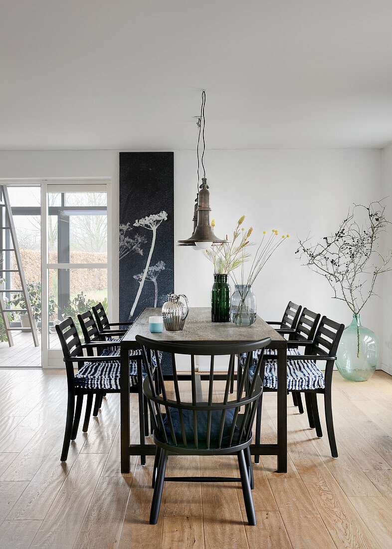 Black chairs around table in dining room with botanical decorations