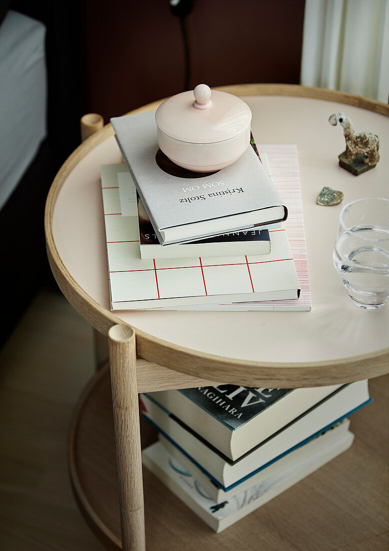 Books and porcelain pot with lid on round bedside table