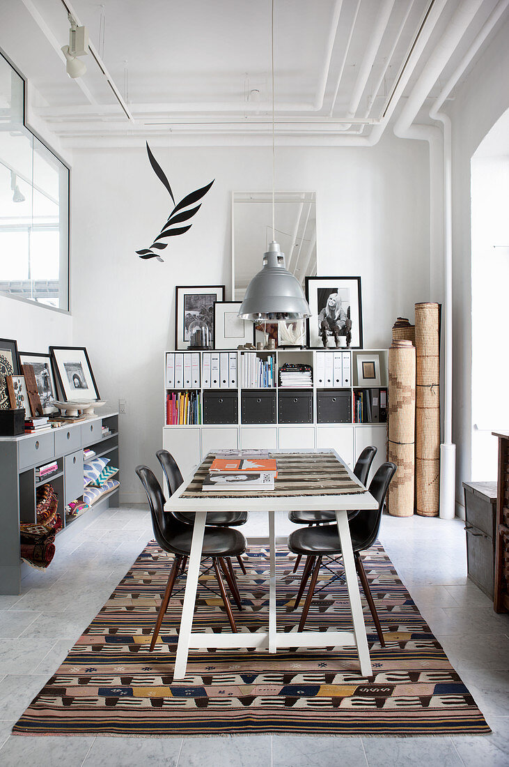 Conference table and classic chairs on kilim rug with filing cabinet in background