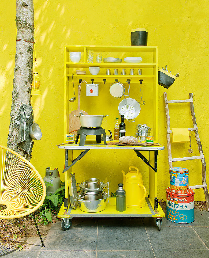 Outdoor kitchen with gas hob against yellow wall