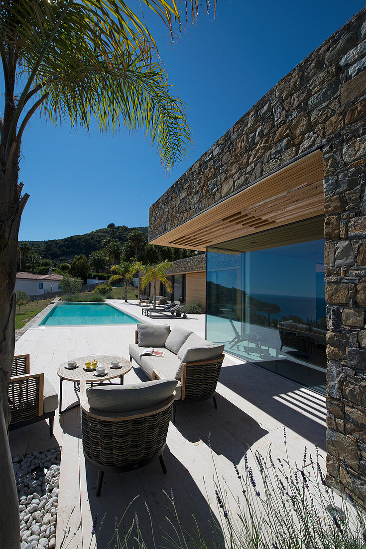 Lounge furniture on terrace of modern house with swimming pool