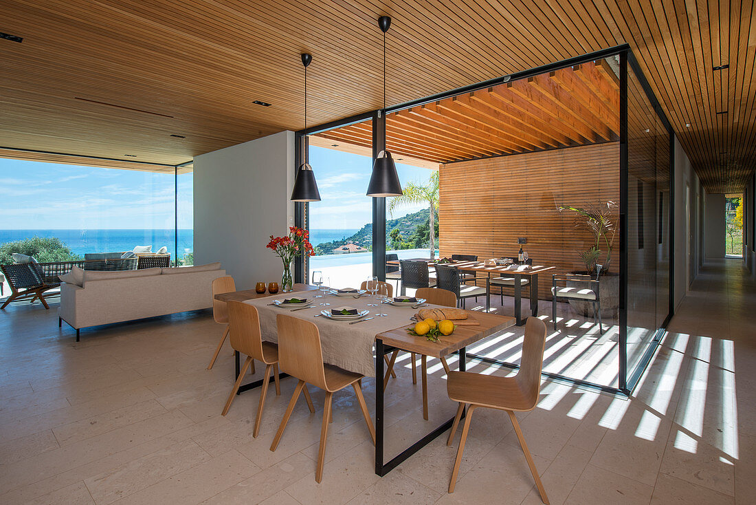 Dining table in open-plan interior of modern, architect-designed house