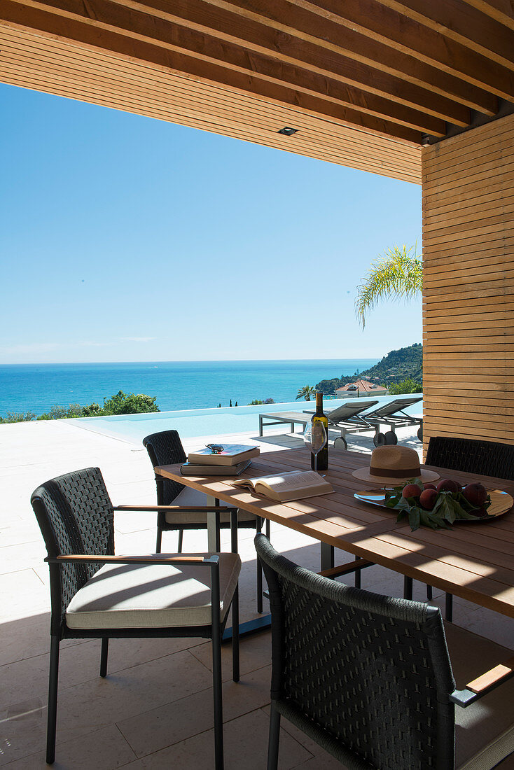 Dining table on roofed terrace with swimming pool and sea view