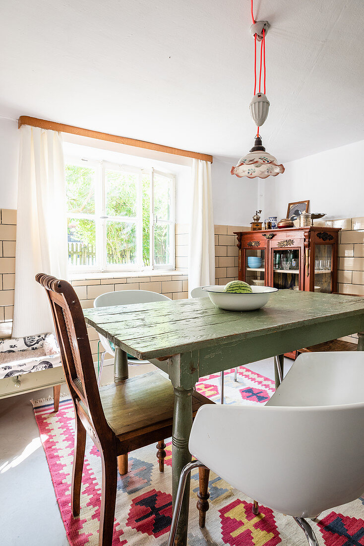 Various chairs around old table in dining room with tiled walls