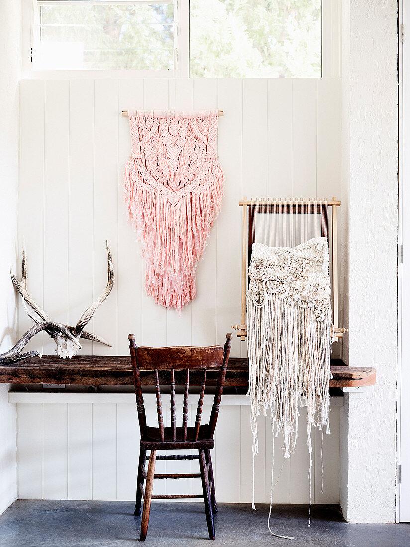Makramee an der Wand und am Webrahmen auf rustikalem Holztisch