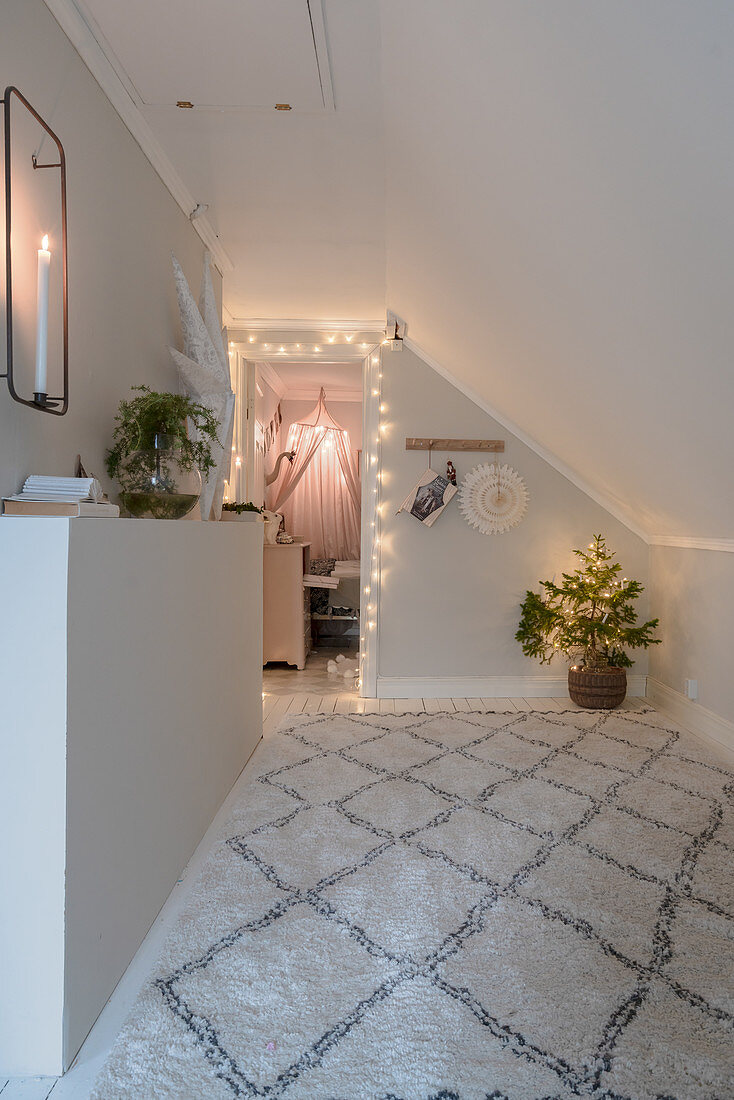 Diamond-patterned rug and Christmas decorations in corridor with sloping ceiling
