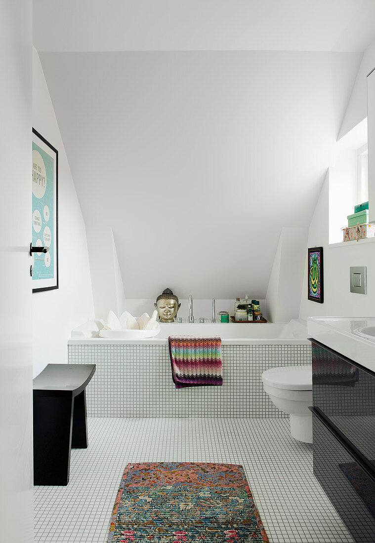Mosaic tiles and fitted bathtub in bathroom with sloping ceiling