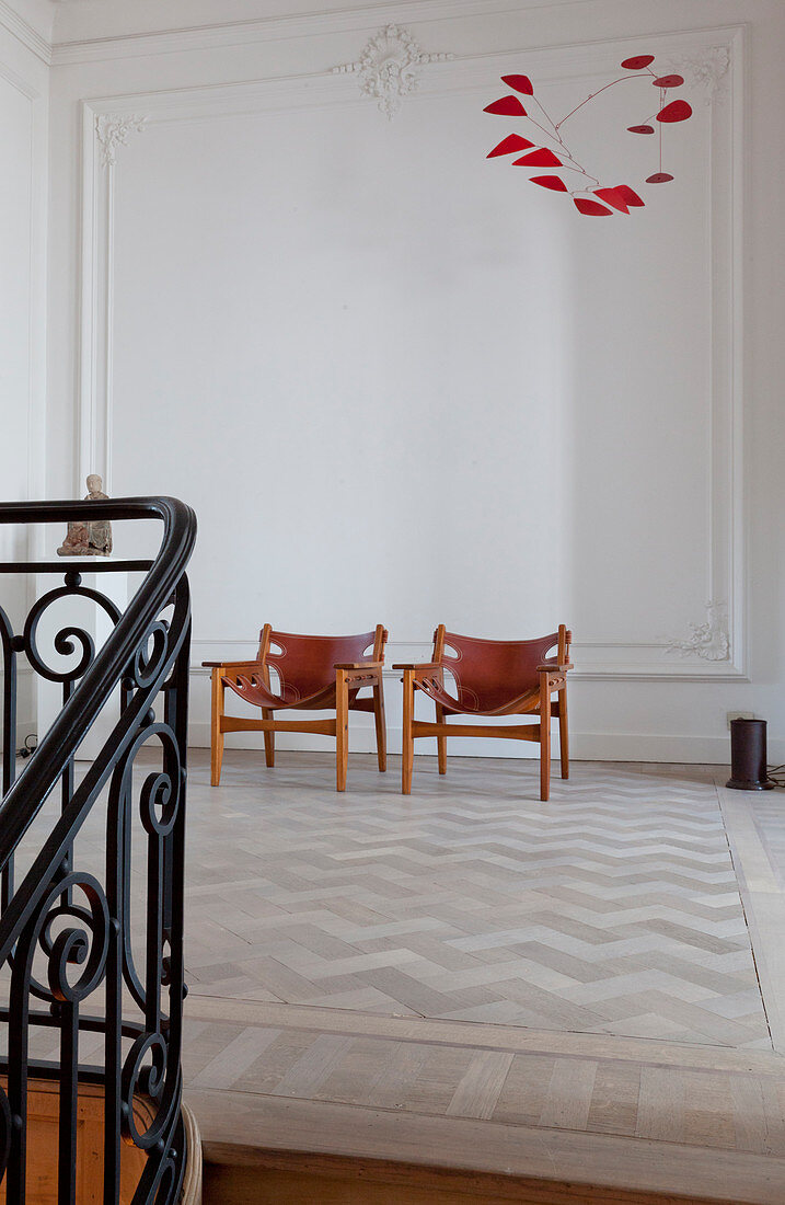 Leather designer chairs against white wall