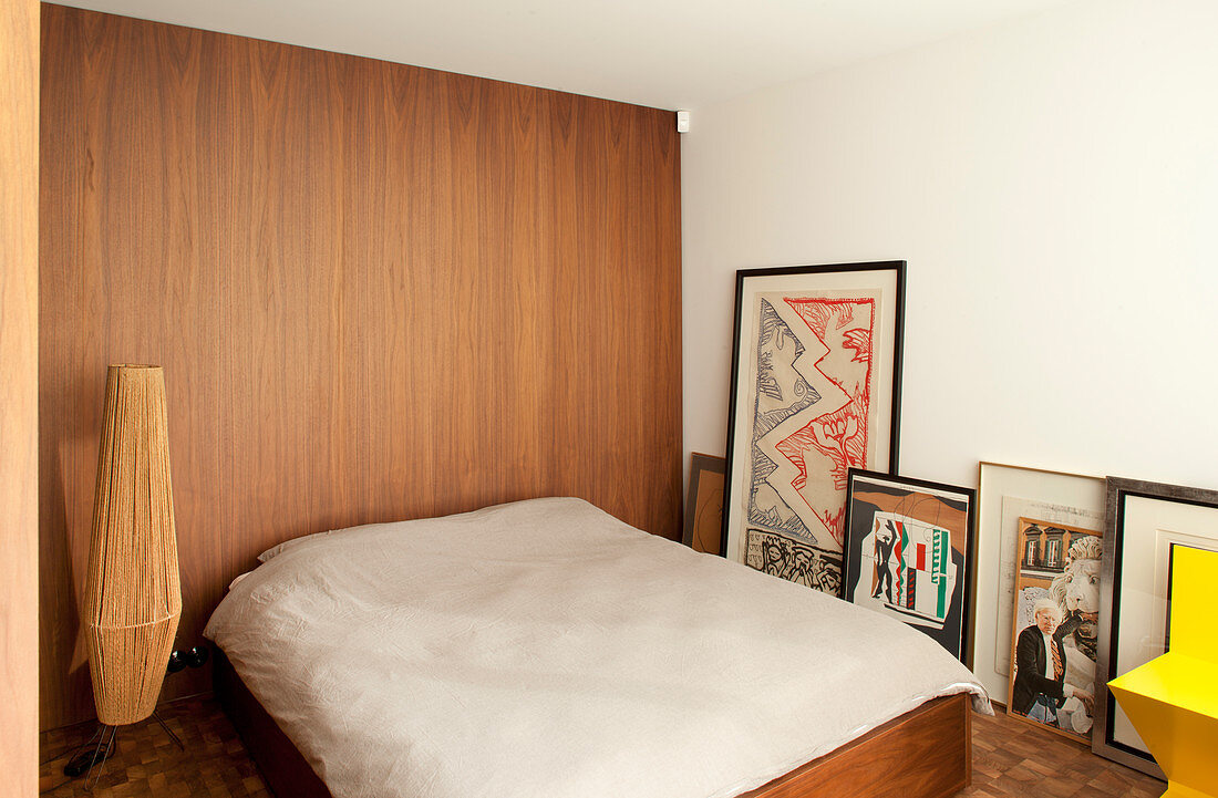 Double bed against wood-clad wall and artworks on floor leaning against white wall
