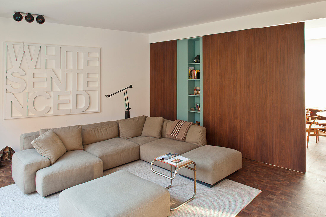 Pale sofa set next to wooden sliding doors in living room