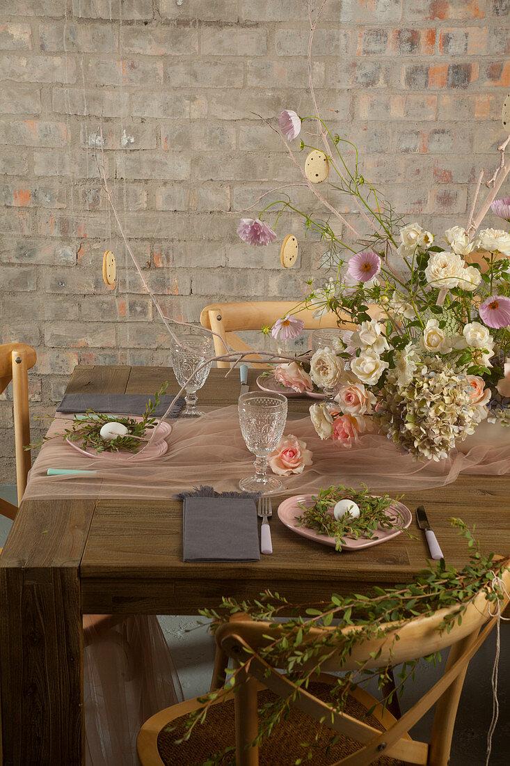 Blumenstrauß auf gedecktem Tisch mit Eiern in Nestern aus Zweigen