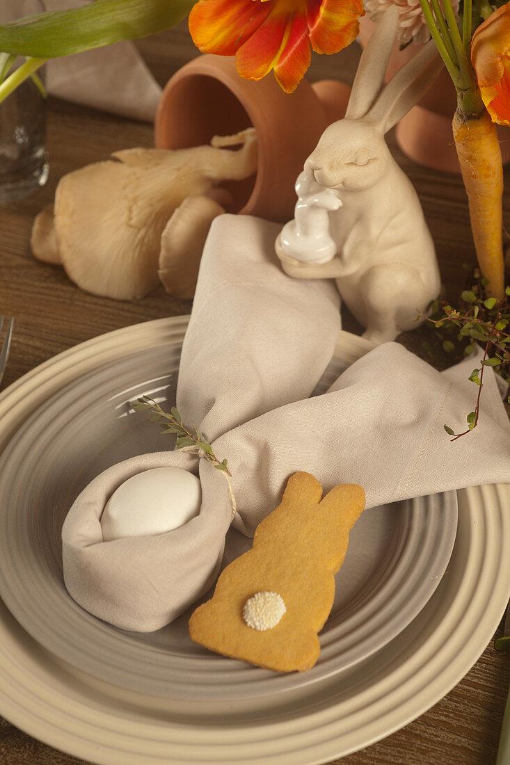 Ei mit Hasenohren aus Serviette und Plätzchen auf dem Ostertisch