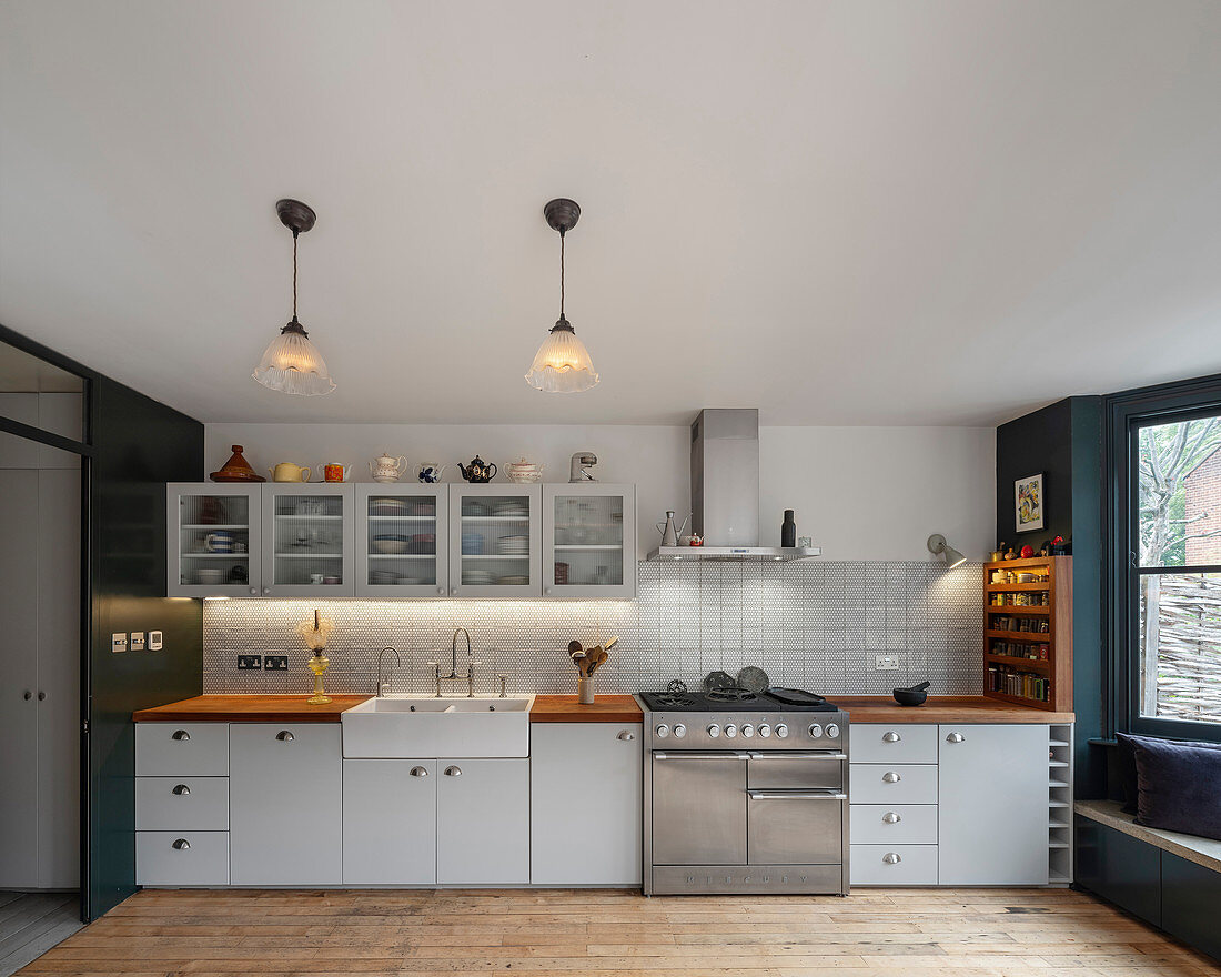 Classic kitchen in white with glass-fronted wall units and gas cooker