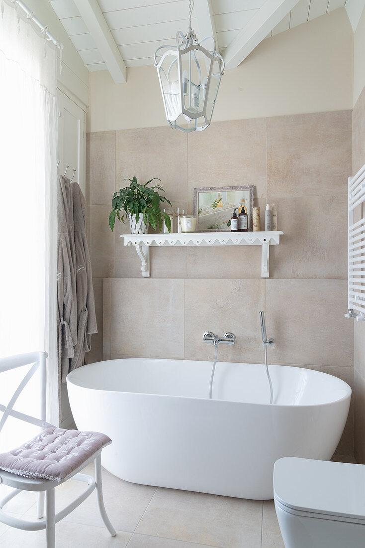 Free-standing bathtub in white and beige bathroom