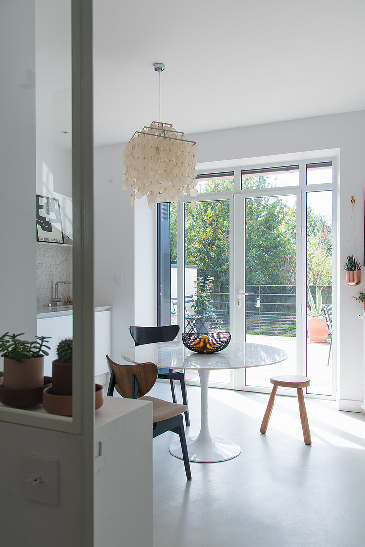 Round classic table next to French windows in kitchen