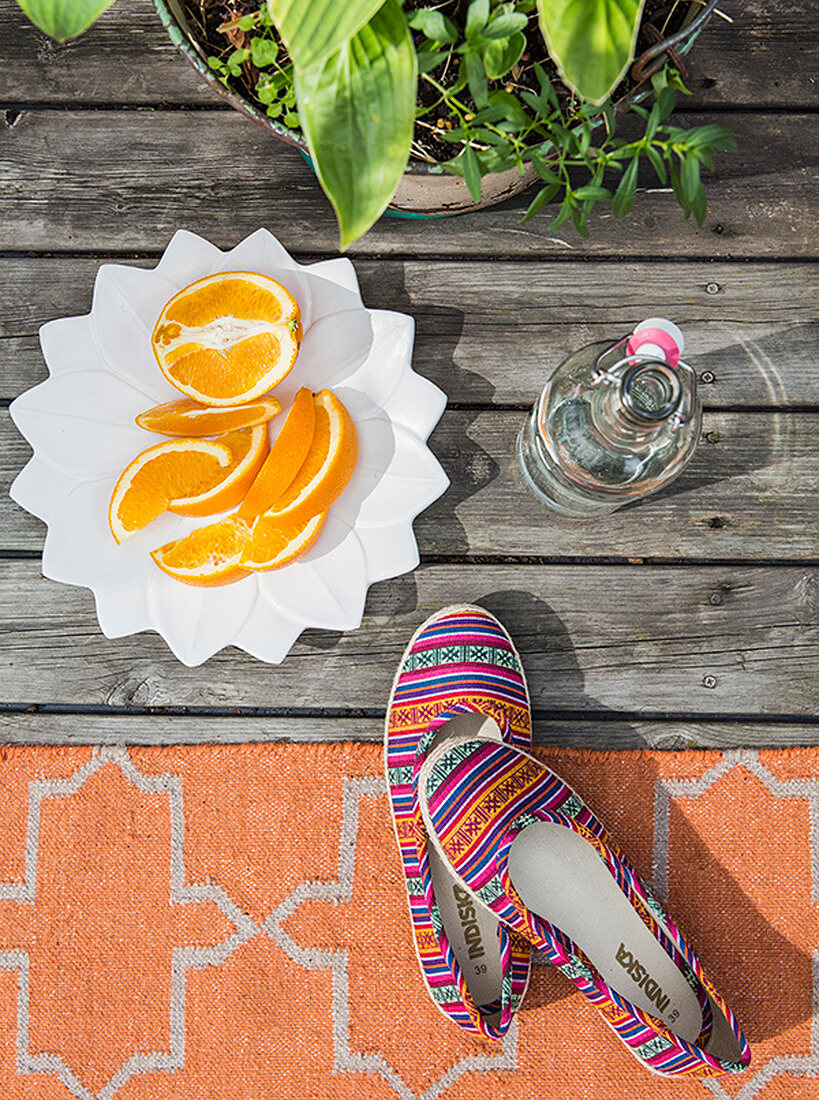 Orange segments on white plate, plant, swing-top bottle and colourful shoes on rug