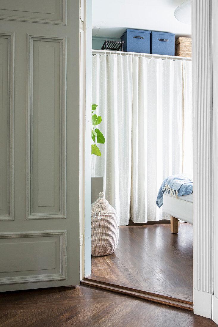 View through open door in bedroom with wardrobe behind curtain