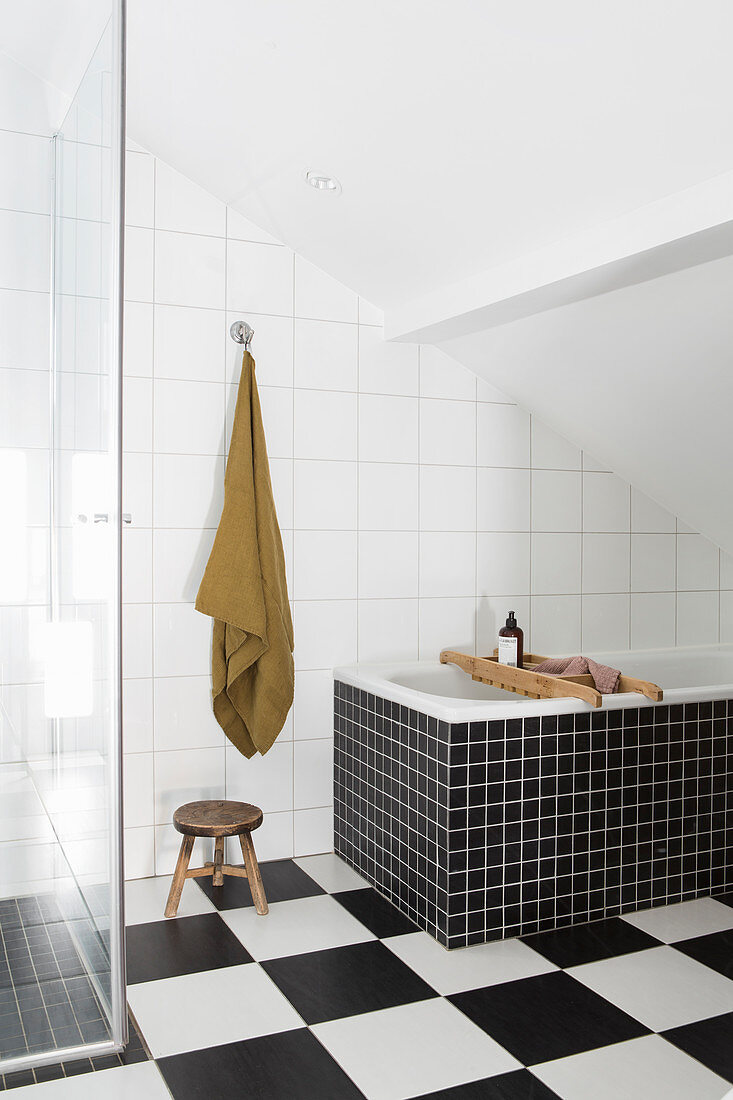 Bathtub on chequered floor below sloping ceiling