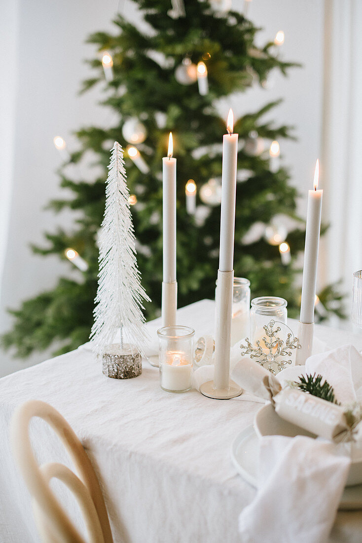 Candles on table set for Christmas in shades of cream