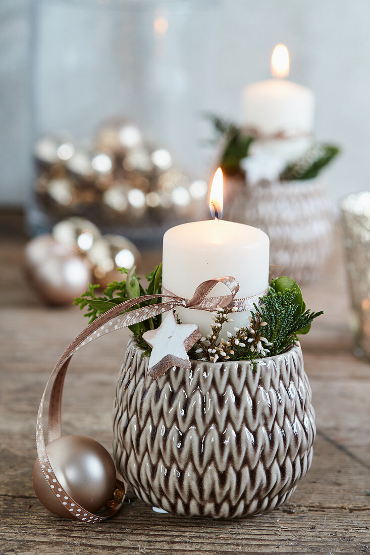 Wintry arrangement of candle and dried flowers in flower pot with structured surface