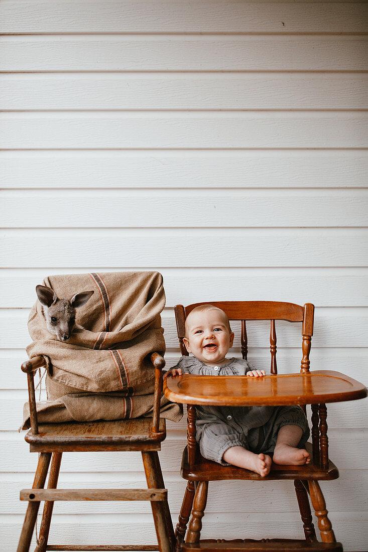 Lachendes Baby im alten Kinderhochstuhl neben einem Känguru