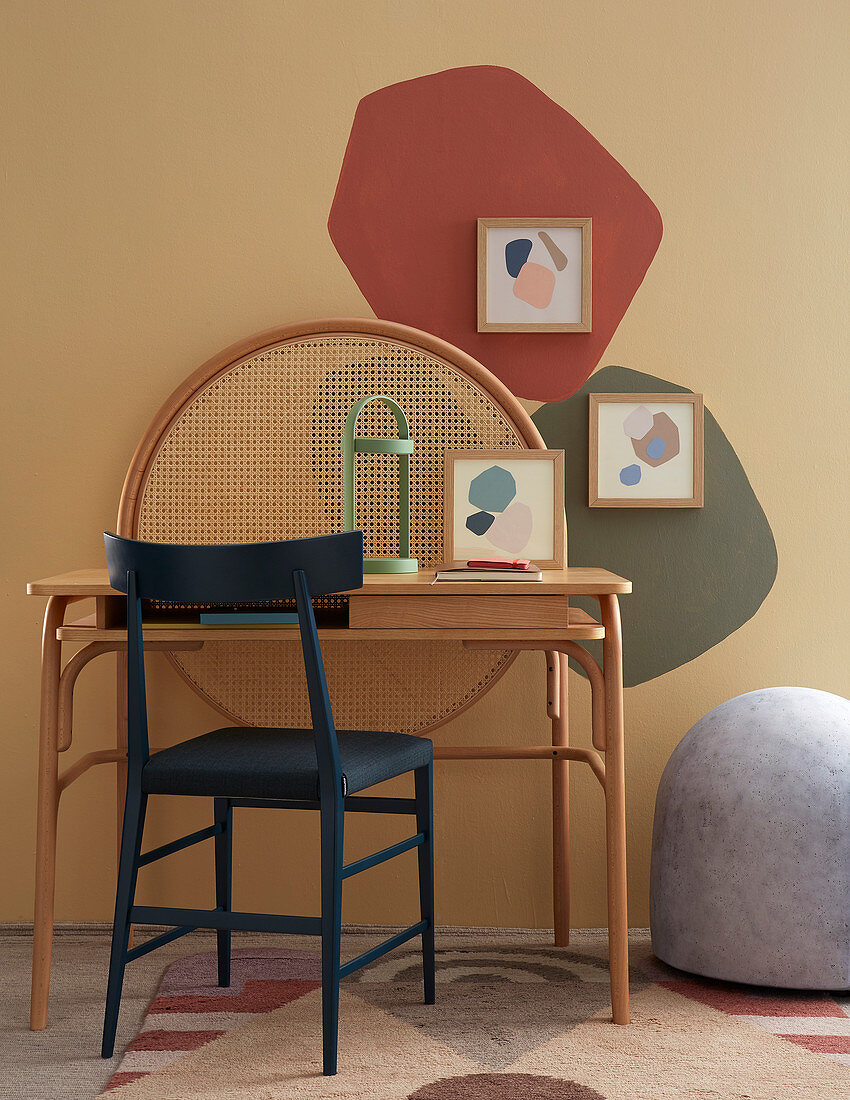 Blue chair and desk in front of patches of colour on wall