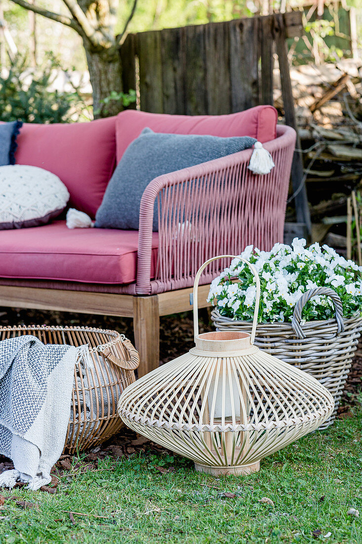 Sofa, planters and planted basket in spring garden