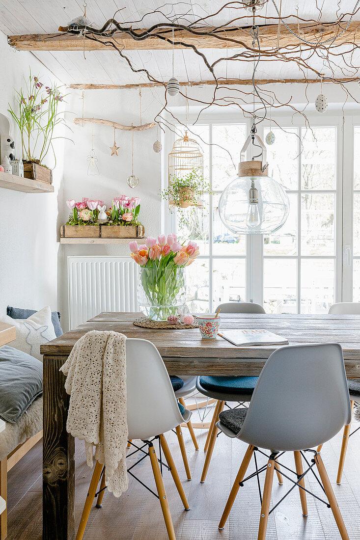 Graue Schalenstühle am Holztisch im Esszimmer mit Frühlingsdeko