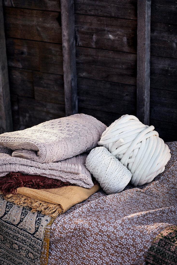 Stapel gefaltete Decken, Garnrolle und Wollknäuel vor Bretterwand