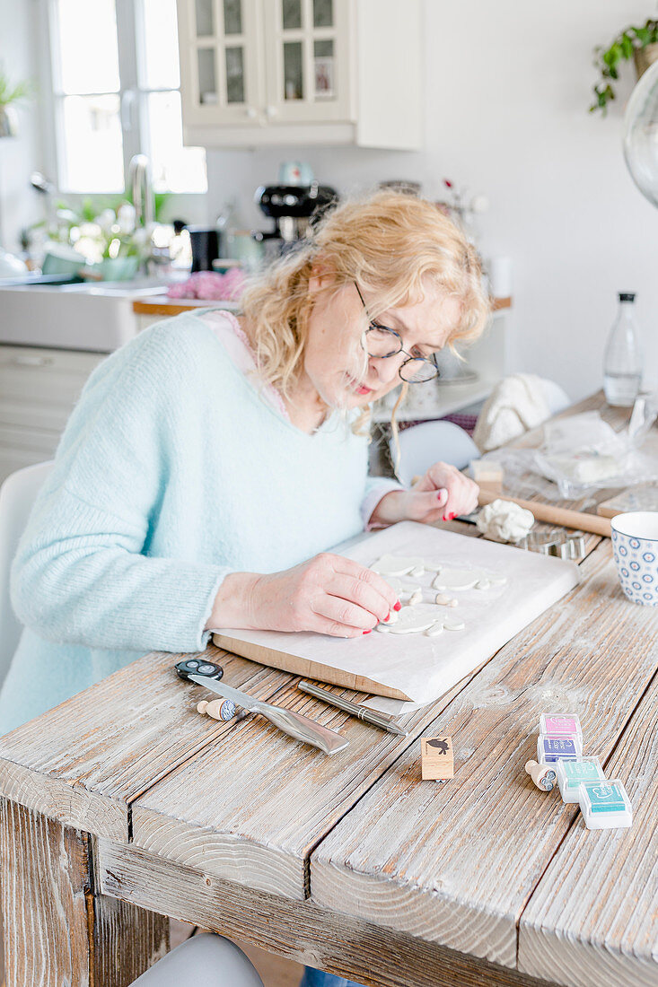 Woman seated at dining table making Easter pendants from modelling clay
