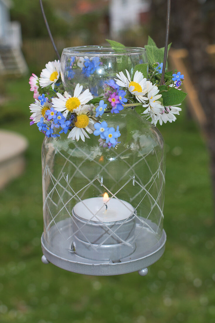 Lantern with spring wreaths made of daisies and forget-me-nots