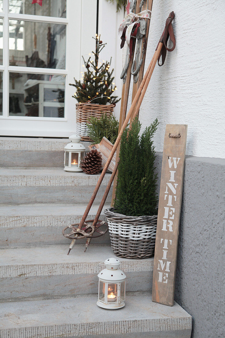 Wintry arrangement of old skis, ski poles, lanterns and potted conifers on steps