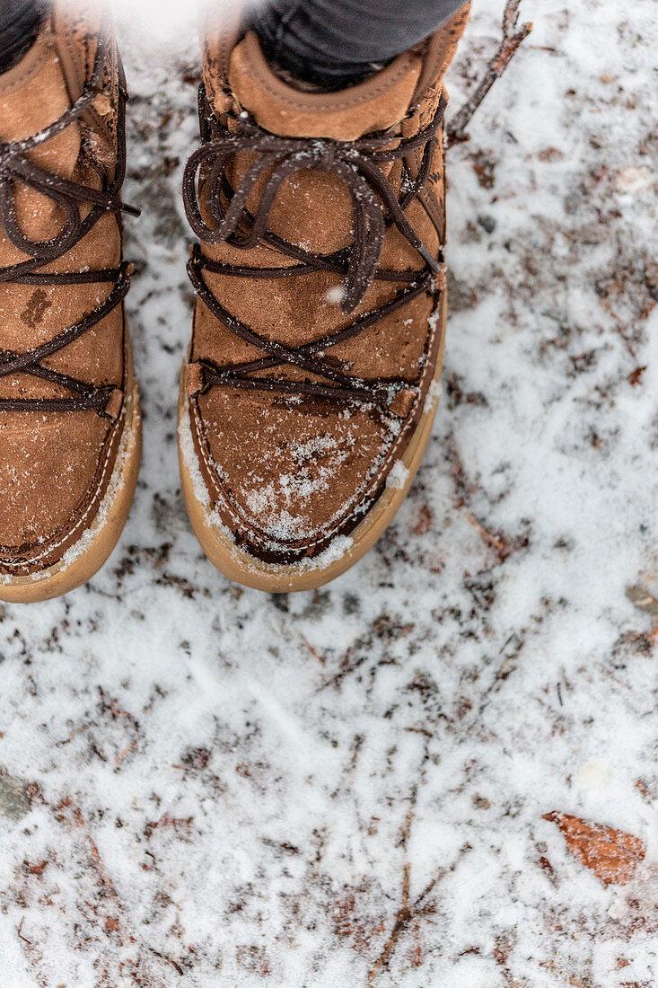 Feet wearing winter shoes in snow