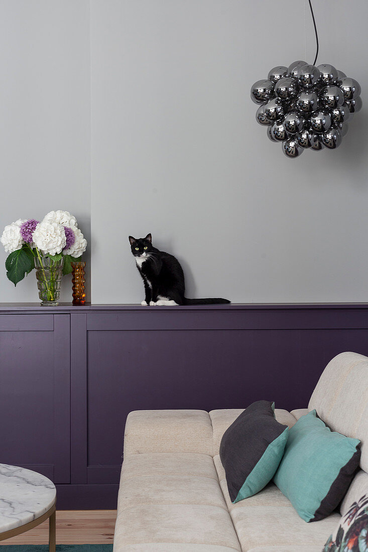 View past pale sofa to cat sitting on ledge of wainscoting