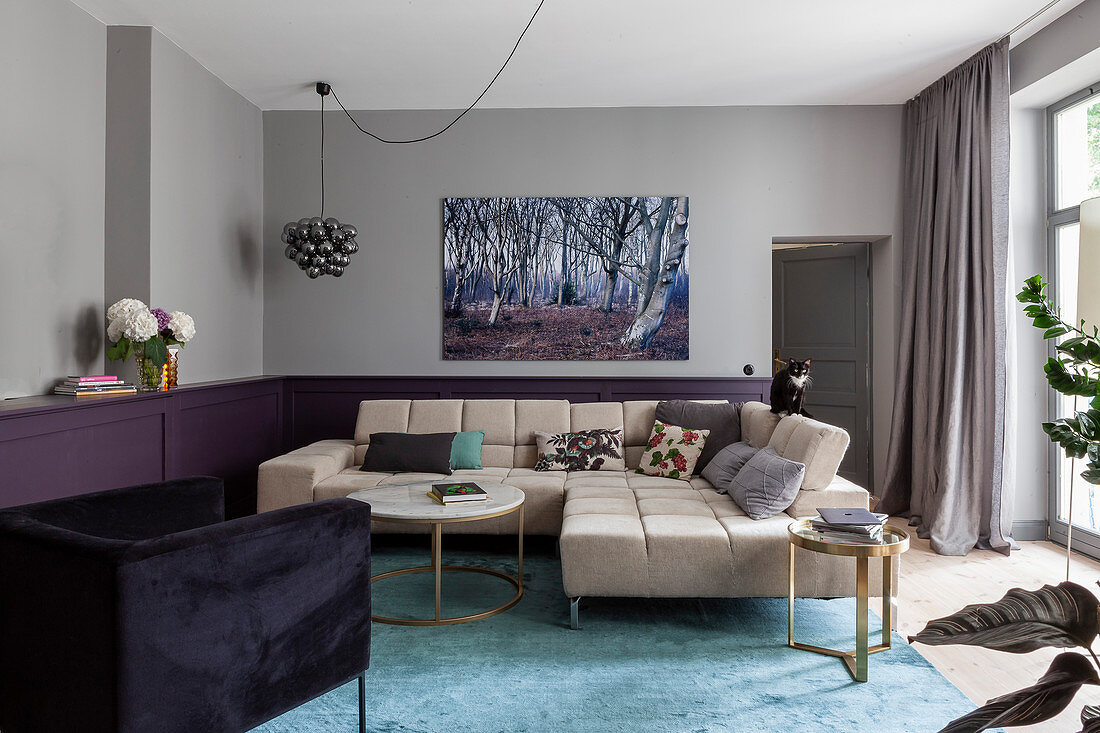 Beige sofa set in living room with purple wainscoting