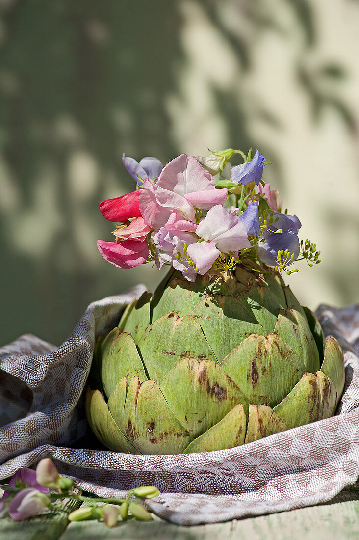 Posy of sweet peas and dill in artichoke