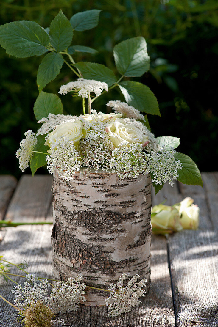Bouquet of roses and Queen Anne's lace in vase made from birch branch