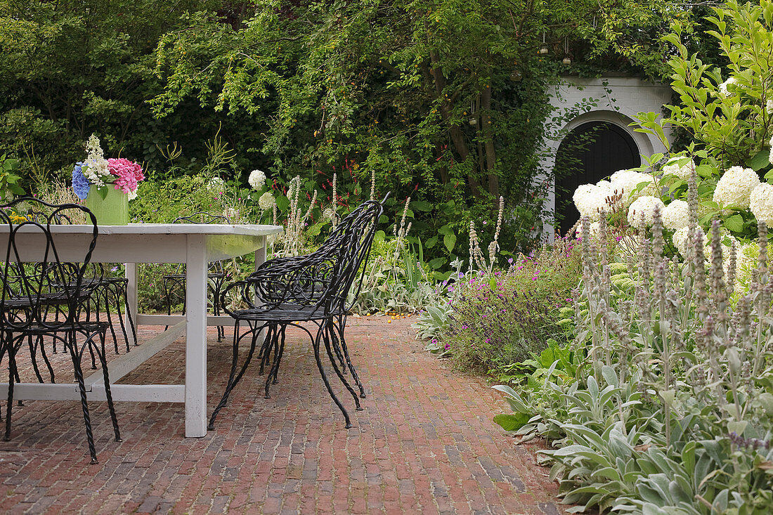 Table and wrought iron chairs on brick terrace