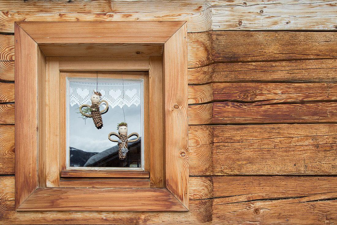Engel aus Tannenzapfen im Fenster eines rustikalen Holzhauses