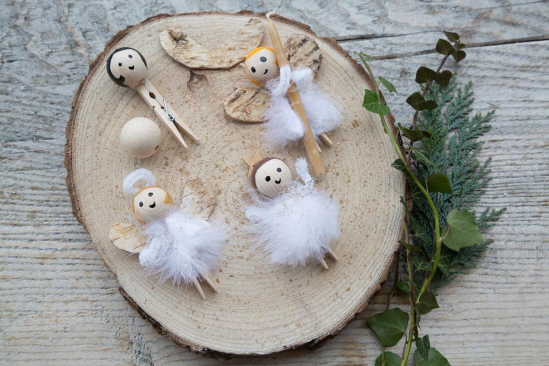 Selbstgemachte Engel aus Rinde, Holzklammern, Holzperlen, Federn
