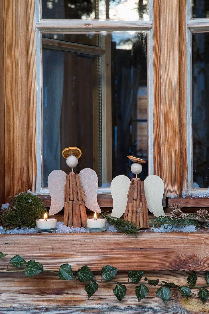 Engel aus Zimtstangen, Teelichter und Efeu am ländlichen Fenster