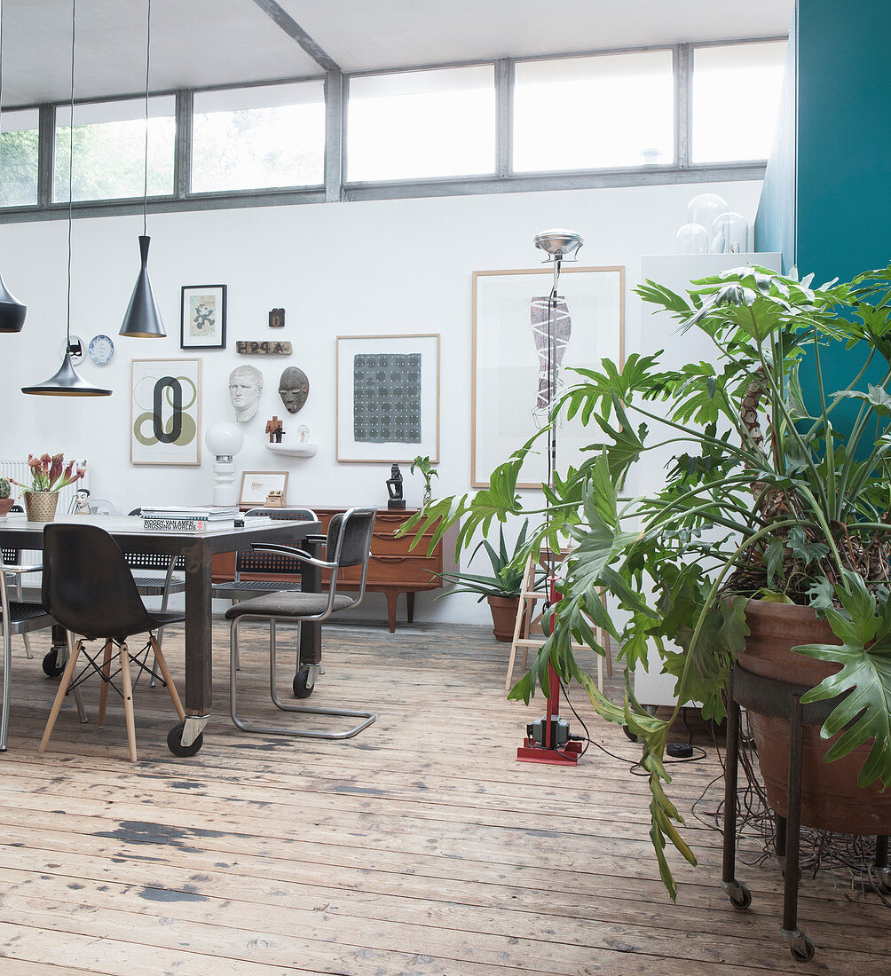 A dining table with classic chairs on wooden floorboards in a loft apartment