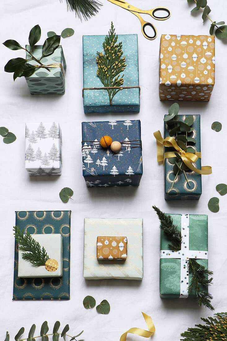 Gifts festively wrapped in shades of green and decorated with twigs