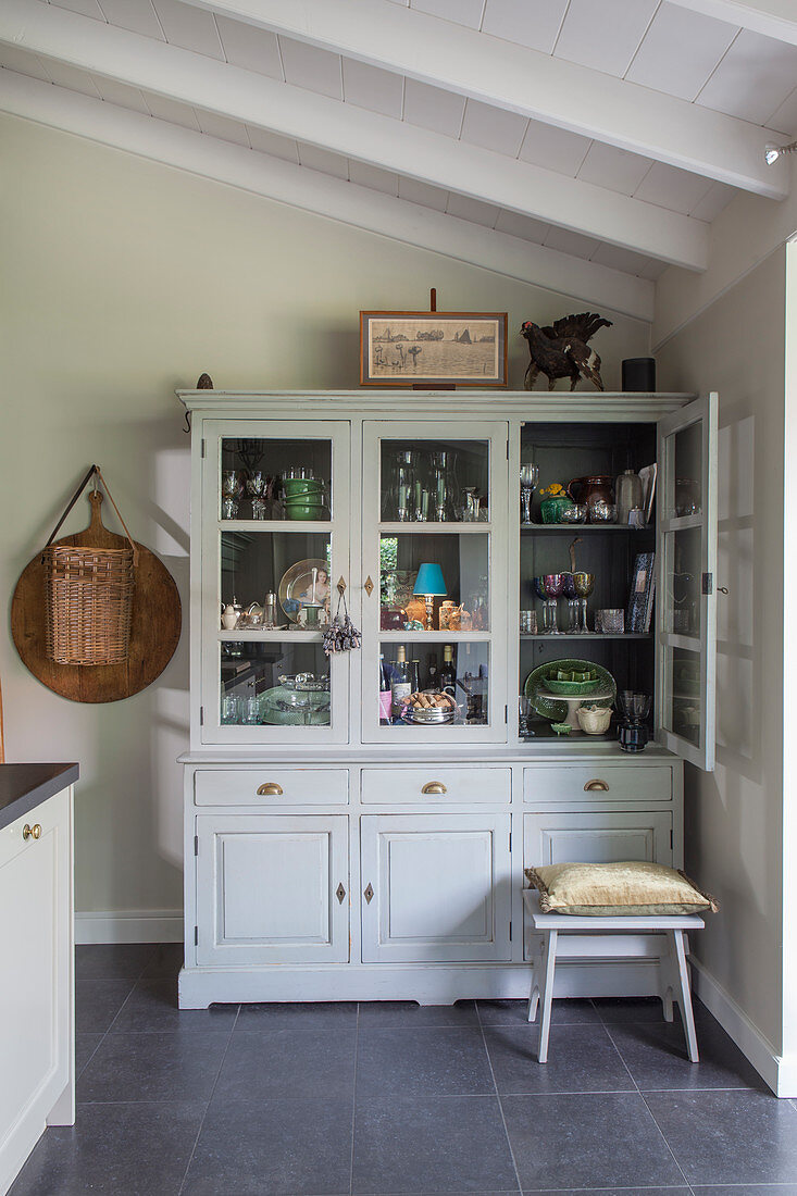 Crockery and glasses in a grey rural-style kitchen cabinet