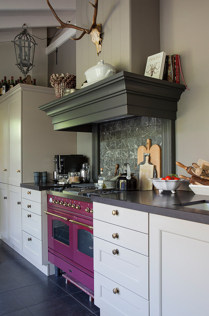 A pink oven in a classic grey kitchen with an extractor hood