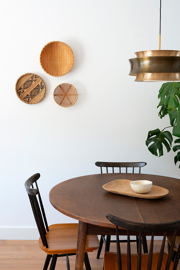 Arrangement of three baskets on wall above round table and spoke-back chairs